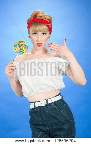 Pin up girl with candy lollipop on bright blue background