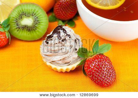 Lemon,lemon Tea,mandarin,kiwi,cake And Strawberries Lying On The Orange Fabric