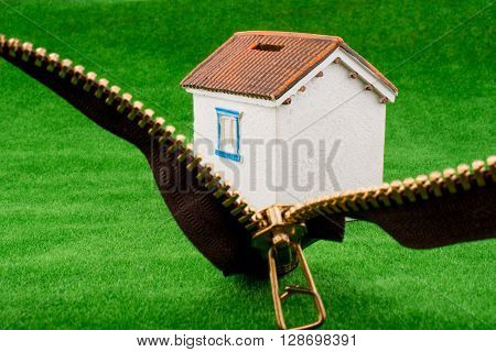 House model through a zipper on green grass