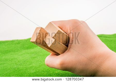 Wooden domino pieces in hand on green grass