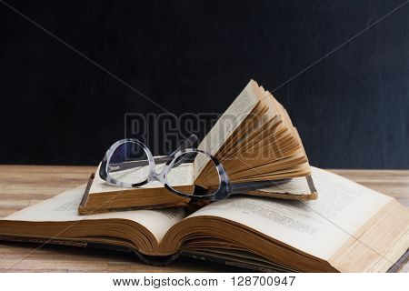 Open books and glasses on wooden table desktop