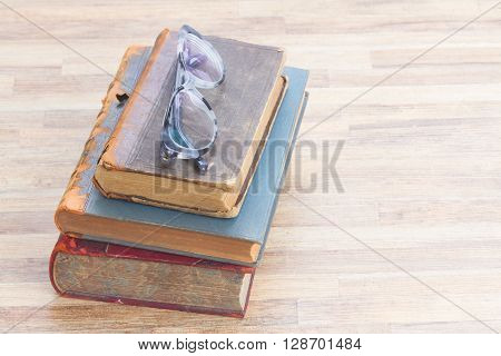 Books stack and glasses, copy space  on wooden table desktop