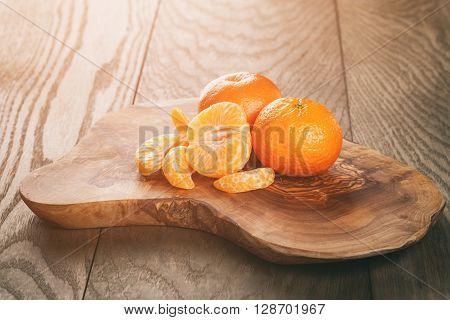 ripe tangerines peeled on wood table, vintage toned