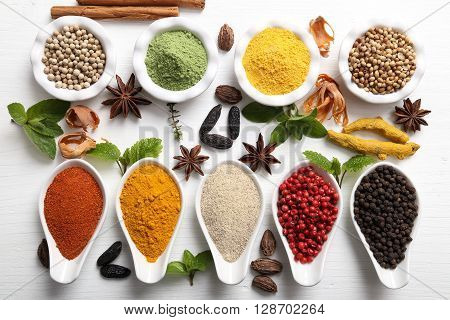 Colorful aromatic Indian spices and herbs on a white wooden background.