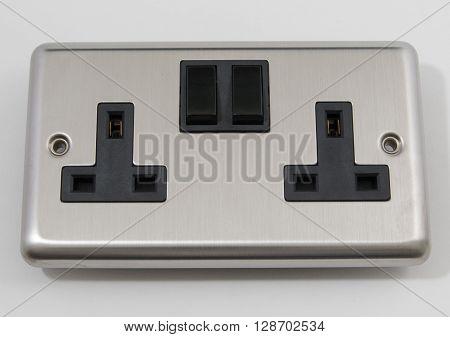 UK Chrome Mains Plug Socket on a plain background