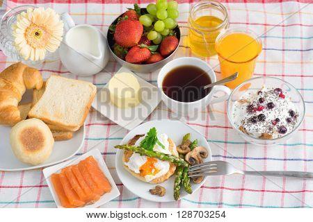 Breakfast with tea, orange Juice, poached egg, salmon, asparagus, berries, Porridge seeing from the top view