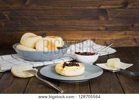 English muffins with jam and butter on wooden background in rustic stile