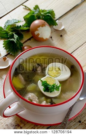 Soup Of Young Nettle With Meat And Egg On A Wooden Background.