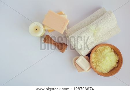 Composition of spa treatment on white background. Spa and wellness setting with natural soap sea salt and towels in pastel yellow green and brown colors. Top view. Copy space.