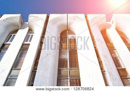 High building of futuristic design made of concrete and glass - architecture modern background. Perspective bottom view architecture cityscape in bright sunlight.