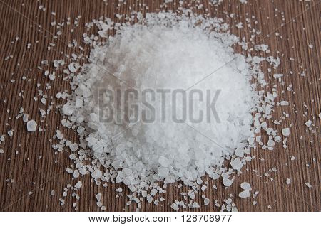 Sea salt on a wooden brown background