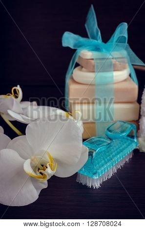 Spa setting in white and blue colors with different kind of natural soaps and orchid on dark wooden background. Tower stack of different handmade soaps. Selective focus.