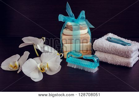 Spa setting in purple and blue colors with different kind of natural soaps soft towels and orchid on dark wooden background. Tower stack of different handmade soaps. Selective focus.