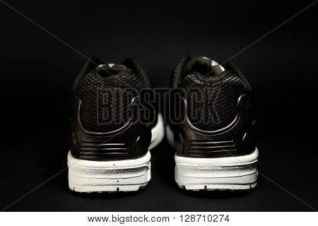 Stylish Black And White Mens Sneakers On Black Background, Advertising Concept
