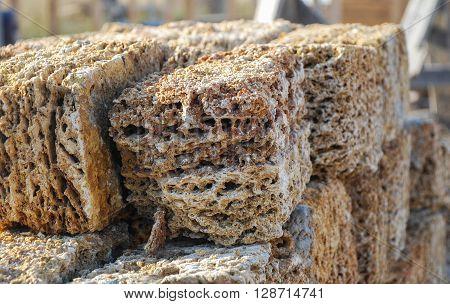 Rectangular blocks of porous limestone stacked in a pile