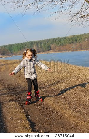 young beautiful girl goes in roller skates on the ground