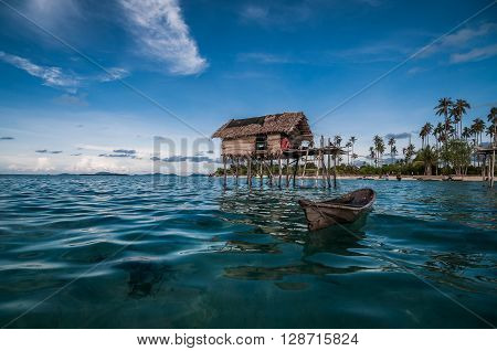 A shot of a boat and a house built on stilts taken at one of the small islands in Sabah Malaysia.