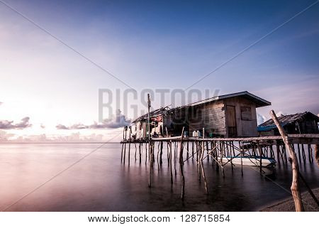 A long exposure shot of houses built on stilts taken during sunset. The shot was taken at one of the islands in Sabah Malaysia.