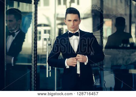 Young Man In Suit Near Glass Door