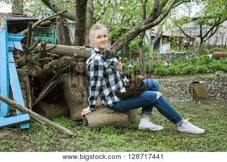 happy pretty girl sitting in the village garden smiling and holding a rabbit in her hands on her lap sitting cat