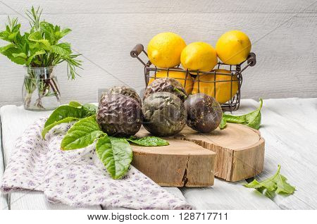 Passion fruits with leaves lemons and herbs in jar on the vintage wooden table.