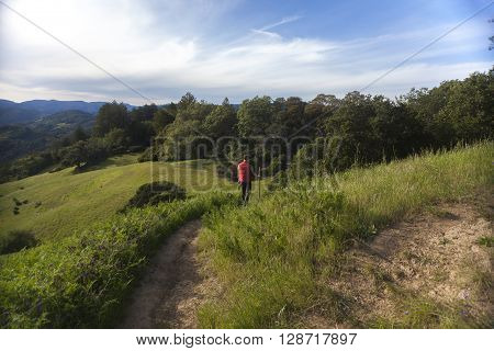 Man in red vest hiking in the green countryside of Sonoma County, California.