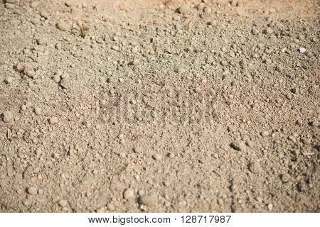 Brown lumpy soil in a shady light as a background