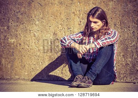 Man Long Haired Sitting Alone Sad On Grunge Wall