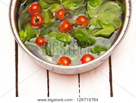 Fresh Spinach And Cherry Tomatoes In A Pan Of Water