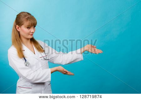 Medicine and healthcare. Portrait of young smiling female doctor. Woman professionalist in white medical uniform showing copy space.