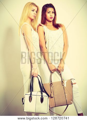 Fashion accessories clothing for ladies. A shot of two young models with handbags. Attractive girls wearing white the same clothes.