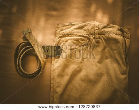 Vintage chino pants and army belt for men on fabric background
