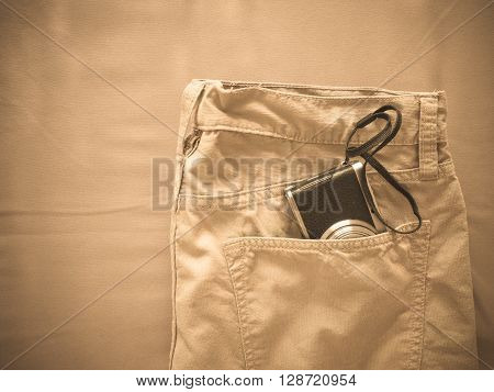 Vintage chino pants and camera for men on fabric background