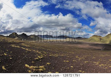 National Park Landmannalaugar in July. Green and pink mountain slopes and snowy white residues from last winter