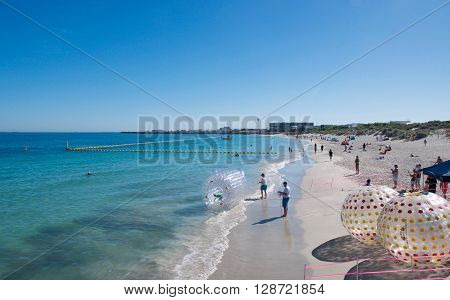 COOGEE,WA,AUSTRALIA-APRIL 3,2016: Coogee Beach Festival with families and floating inflatable water balls in the Indian Ocean waters of Coogee, Western Australia.