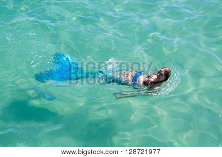 COOGEE,WA,AUSTRALIA-APRIL 3,2016: Live mermaids entertainer floating in the turquoise Indian Ocean at the Coogee Beach Festival in Coogee, Western Australia.
