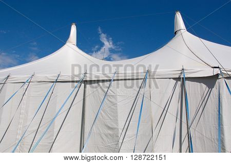 Exterior of vinyl white event tent with blue nylon securing straps under a bright blue sky.