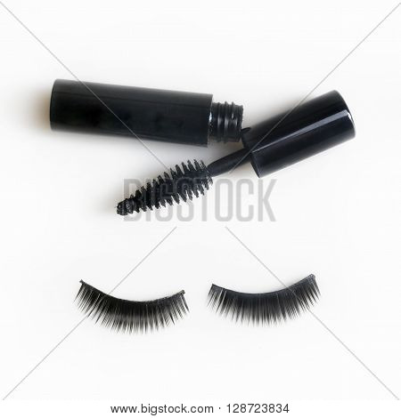 False lashes and black mascara isolated on white