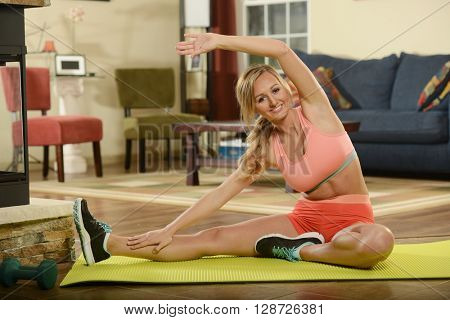 Young woman working out on a mat at home