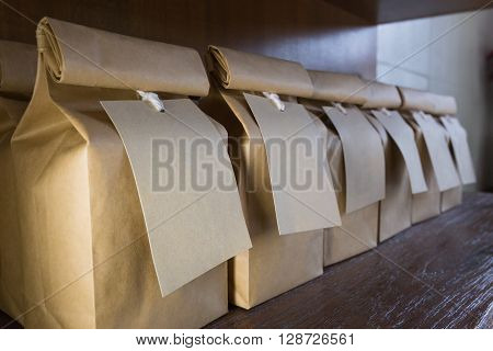 Brown paper bags with brown paper labels hanging from white strings on wooden shelves selective focus on the closest bag's label