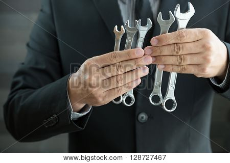 Businessman holding spanners in hand concept fixing