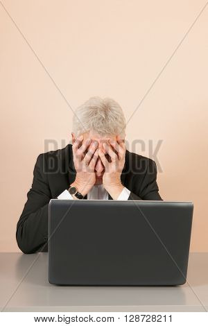 Senior business man crying behind the with laptop