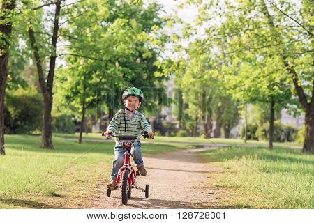 The child riding a bicycle. The kid in a helmet riding a bike in the park. Beautiful baby. Toned image.