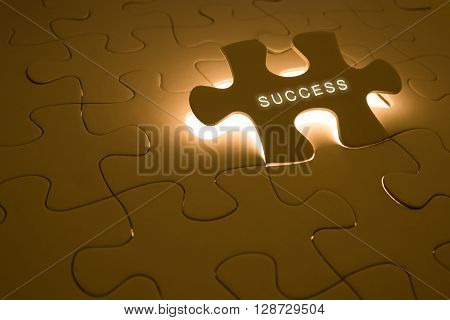 success concept with success word on puzzle and light