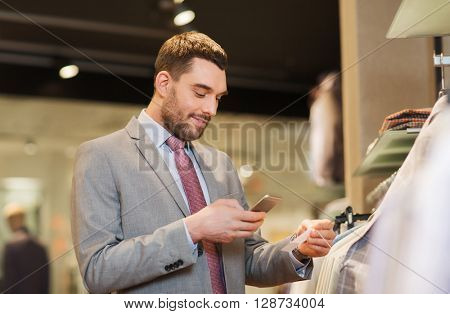 sale, shopping, fashion, technology and people concept - happy man in suit with smartphone choosing clothes at clothing store