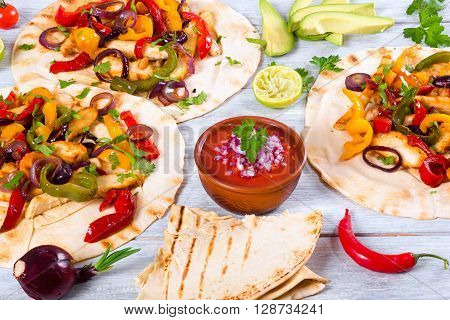 Homemade chicken burritos with vegetables lime and salsa sauce on white wooden background full focus studio lights close-up view from above