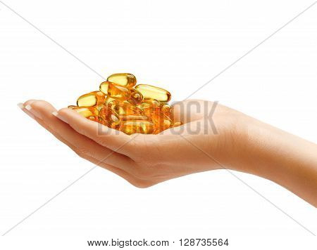 Woman's Hand holding Omega 3 capsules isolated on white background. Palm up close up. High resolution product.