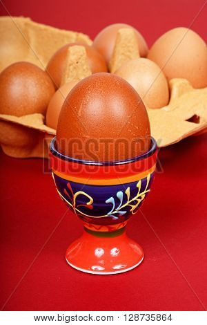 A boiled egg in an eggcup with a carton of eggs to the rear.