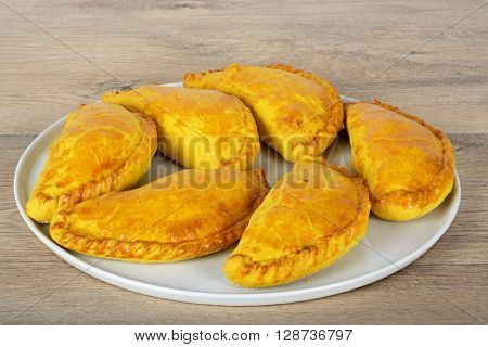 Freshly cooked homemade vegetarian pasties on a white plate against a wooden background.
