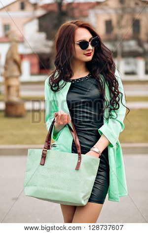Fashion lifestyle portrait of young happy pretty woman laughing and having fun on the party. favorite music at earphones, stylish vintage outfit, bright fresh colors